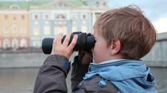 Boy stands on waterfront, looking through binoculars Stock Footage