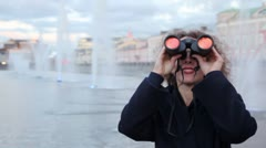 Woman stand on waterfront, looking through binoculars Stock Footage