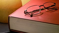 Reading: book and glasses under lamp Stock Footage