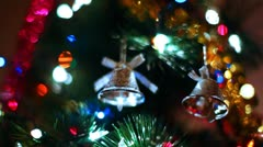 two toy bells hang on Christmas tree among of blinking colored garlands - stock footage