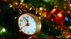 Alarm clock at three minutes remaining before New Years in front of festive Stock Footage