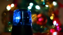 Flashing lamp rotates in front of festive lights Christmas tree Stock Footage