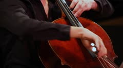 Expressive man plays cello sitting on stage Stock Footage