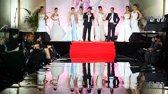 Models in white wedding dresses with leading show stand on stage Stock Footage