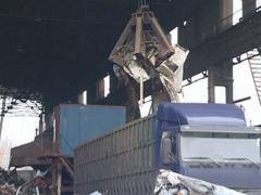 Special crane unloads scrap metal from the truck. - stock footage
