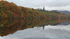 Autumn colours reflected in Loch Faskally near Pitlochry Scotland Stock Footage