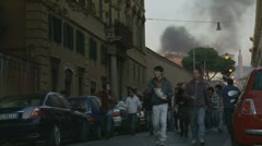 Youths walk from riot in Rome, smoke in the sky Stock Footage