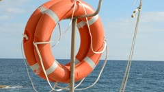 Life ring floating on top of sunny blue water Stock Footage