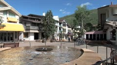 WorldClips-Vail Center City Fountain-Cyclists-ws Stock Footage