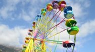 Big wheel with multicolored cabins in amusement park Stock Footage