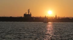 Sunset with sailboat USN Ronald Reagan Stock Footage