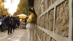 Girl posing toward camera by stone wall of Deoksugung Palace in Seoul Stock Footage