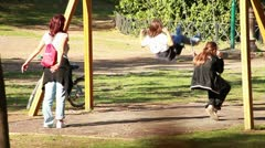People at park - child on swing Stock Footage