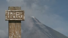Ash Rises From Top Of Large Volcano Behind Religious Sign Stock Footage