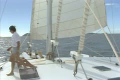 Pan up from deck of sailing boat to sail - stock footage