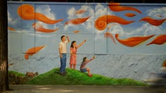 Timelapse of traffic and pedestrians passing by mural of happy family Stock Footage