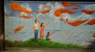 Stock Video Footage of Timelapse of traffic and pedestrians passing by mural of happy family