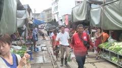 Train drives through the middle of a market in Thailand Stock Footage