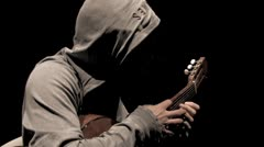 Hooded guitarist in dark room - 2 handed tapping technique HD Stock Footage