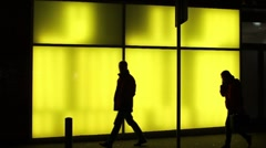 Silhouettes in front of illuminated glass wall Stock Footage