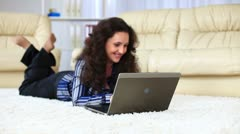Young adult with laptop lying on carpet. She smiles. DOLLY HD Stock Footage