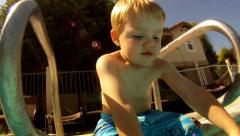 Young boy playing poolside with football underwater hot day summer fun happy Stock Footage