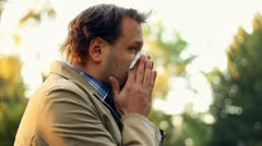 Sick man blowing his nose into tissue, outdoors HD Stock Footage