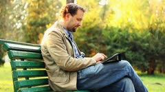 Young happy man with tablet computer sitting in the park HD Stock Footage