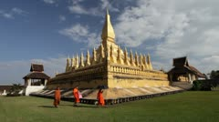 Three monks walking in front of golden pagoda, Laos Stock Footage