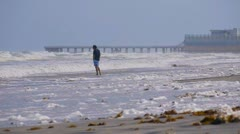Man on the beach looking at rough surf Stock Footage