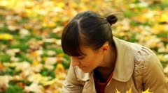 Young happy woman picking up golden leaves in beautiful autumn park HD Stock Footage