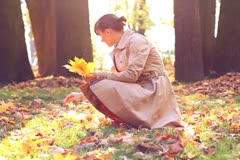 Young happy woman picking up golden leaves in autumn park, slow motion NTSC Stock Footage