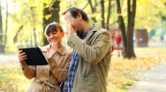 Young couple with tablet computer in autumn park Stock Footage