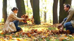 Young couple having fun in beautiful autumn park, slow motion Stock Footage