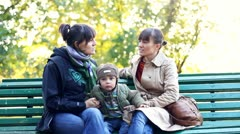Two female friends with young boy sitting on bench in city park Stock Footage
