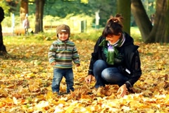 Young mother having fun with her son in autumn park, slow motion - stock footage