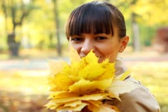 Young happy woman with maple golden leaves walking in beautiful autumn park Stock Footage