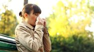 Stock Video Footage of Sick woman blowing her nose into tissue, outdoors