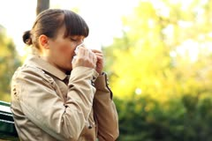 Sick woman blowing her nose into tissue, outdoors - stock footage