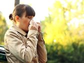 Sick woman blowing her nose into tissue, outdoors Stock Footage