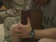Soldiers holding bibles with heads bowed in prayer Stock Footage