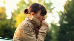 Sick woman sitting on park bench and coughing - stock footage