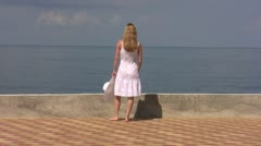 Woman with white hat stand and looks at sea Stock Footage