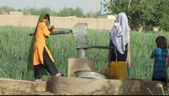 Afghan woman and children at water pump(HD) C Stock Footage