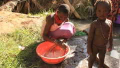 Woman washing necklace in container by stream - stock footage