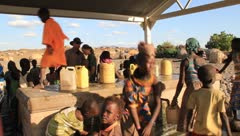 Girl getting water then carrying container on head at water station - stock footage