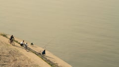 Two old men fishing and one man riding bicycle Stock Footage