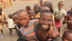 Smiling African children pushing and shoving to get in the picture - stock footage
