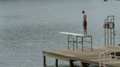 Guy jumping off diving board into lake - stock footage