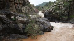 A turbulent, brown river with rocky banks in Israel. Stock Footage
